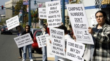In this photo, members of the Calvary Bible Church of Milpitas appear at the closed Family Radio station offices of Harold Camping in Oakland, Calif., to offer support to victims of the radio evangelist, who claimed that the ascension into heaven of the Christian faithful would happen on Saturday, May 21, 2011. (AP / Dino Vournas, File)