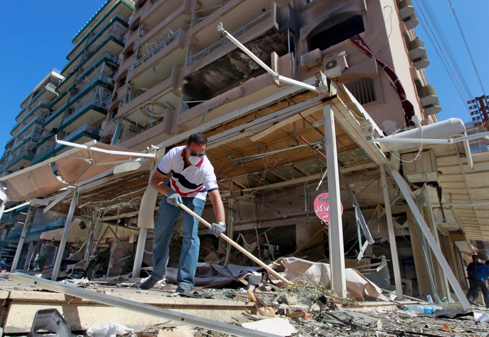 A Lebanese man cleans his damaged shop at the site of a car bomb explosion outside of the Salam mosque in the northern city of Tripoli, Lebanon, Saturday, Aug. 24, 2013.  (AP / Bilal Hussein)