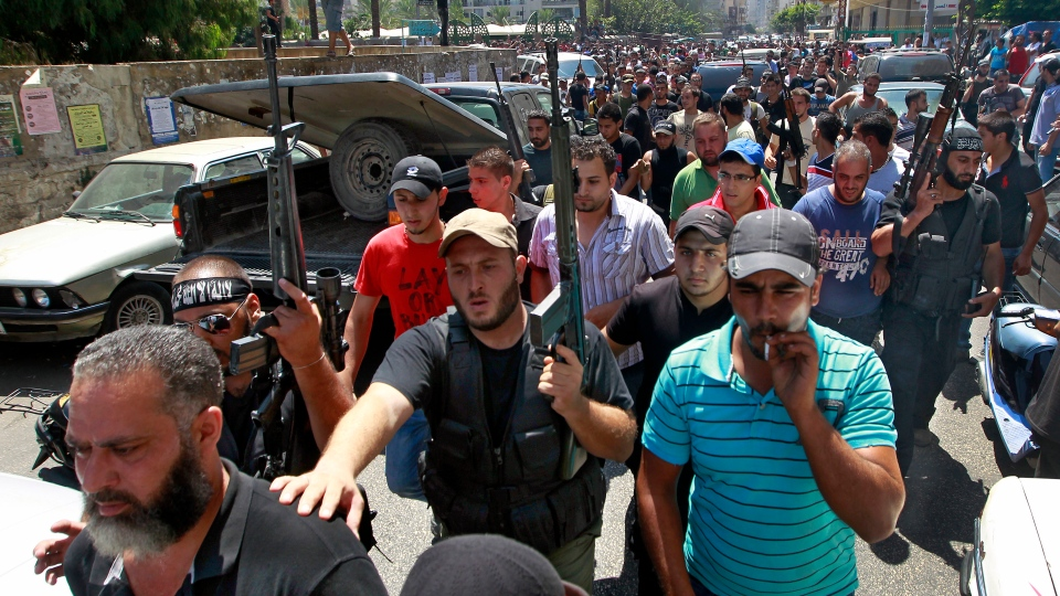 Gunmen fire their weapons during the funeral of a man who was killed in a car bomb attack, in the northern city of Tripoli, Lebanon, Saturday, Aug. 24, 2013. (AP / Bilal Hussein)