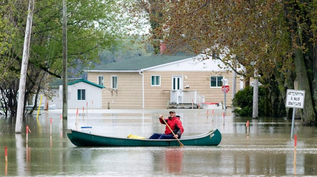 A man paddles canoe through a flooded street in the town of St-Blaise, Que., Tuesday, May 17, 2011. (Graham Hughes / THE CANADIAN PRESS)