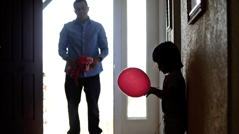 Mireya Salazar stares at a pink balloon as her father Nelson waits for her in the doorway of his parents' house in Denver on Wednesday, March 30, 2011. (AP / The Denver Post, AAron Ontiveroz)