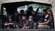 Pakistani army commandos drive through the main gate of a naval aviation base following an attack by militants in Karachi, Pakistan, Monday, May 23, 2011. (AP / Shakil Adil)