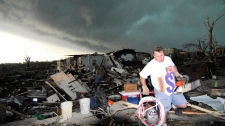 Mark Siler carries some salvageable items from the house of his friend Clay Warden as another storm approaches Joplin, Mo. on Monday, May 23, 2011. (AP / Mike Gullett)