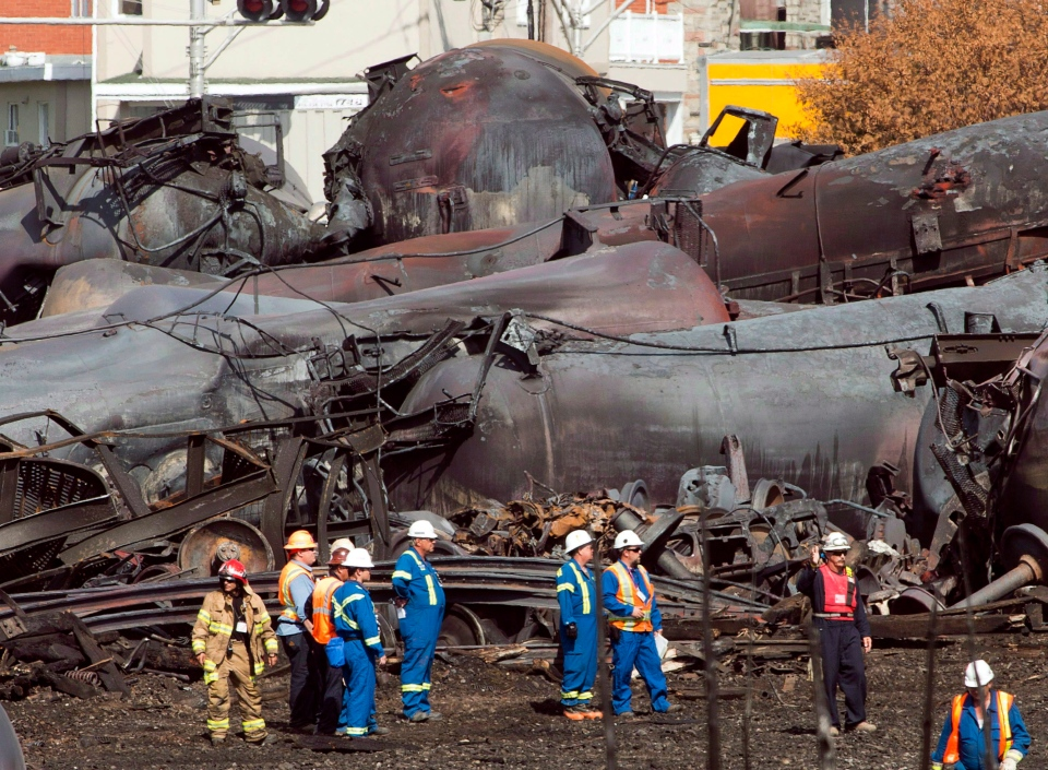 Workers stand before mangled tanker cars at the crash site of a train derailment and fire in Lac-Megantic, Que., Tuesday, July 16, 2013. (Ryan Remiorz / THE CANADIAN PRESS)