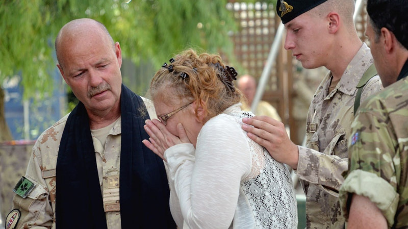 Josee Belisle, mother of Cpl. Yannick Scherrer sobs at the sight of her son's remembrance plaque on the monument to fallen Canadians at Kandahar Airfield, on Tuesday May 24, 2011. She is comforted by Maj. Grahame Thompson, the senior Canadian task force padre and an unidentified friend of her son.
