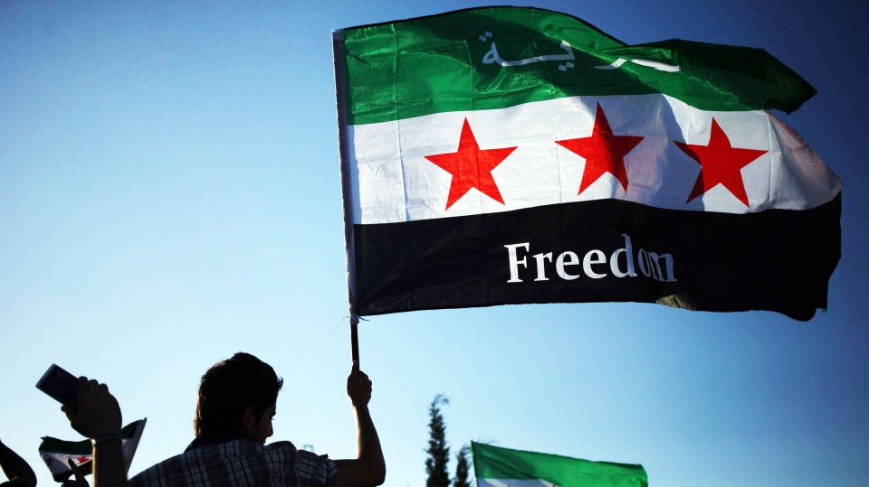 A Syrian protester waves the Syrian revolutionary flag, during a protest in front of the Syrian embassy to condemn the alleged poison gas attack on the suburbs of Damascus, during a protest in front of the Syrian embassy, in Amman, Jordan Aug. 23, 2013. (AP / Mohammad Hannon)