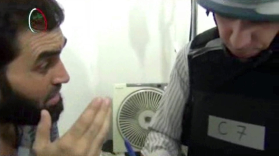 In this Monday, Aug. 26, 2013 image taken from amateur video footage provided by the Media Office Of Moadamiyeh, a UN inspector, right, speaks to a man about the alleged chemical weapon attack as a UN inspection team visits a makeshift hospital in Moadamiyeh, a suburb of the Syrian capital of Damascus.