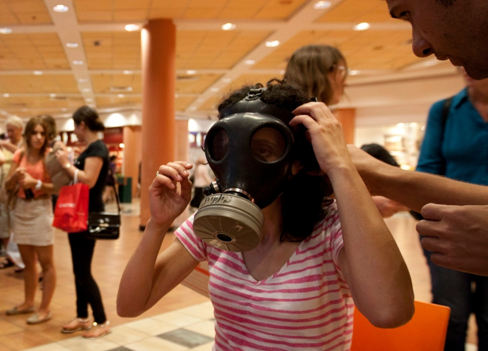 Israeli Hagit Ohana tries on a gas mask at a distribution center in a shopping mall in Mevaseret Zion near Jerusalem, Wednesday, July 25, 2012. (AP / Sebastian Scheiner)
