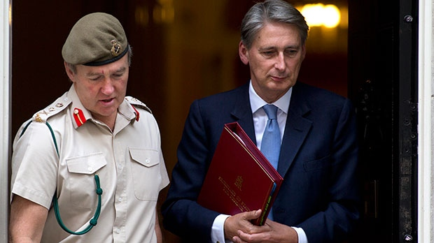 Britain's Defence Secretary Philip Hammond, right, and the Chief of Defense Staff Gen. Nick Houghton leave 10 Downing street following a national security meeting on the situation in Syria at Downing Street in London, Wednesday, Aug. 28, 2013. (AP / Alastair Grant)