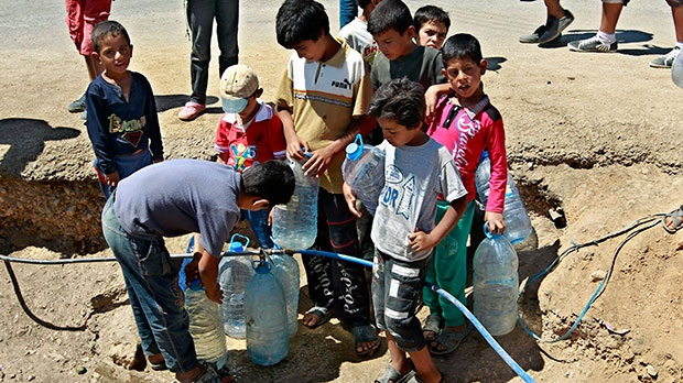 Syrian refugee boys fill up their water bottles, at a temporary refugee camp in the eastern Lebanese town of Faour near the border with Syria, Lebanon, Wednesday, Aug. 28, 2013. (AP / Bilal Hussein)