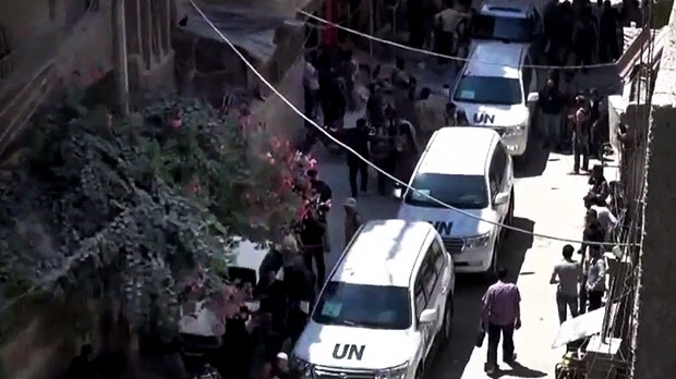 Syrians welcome the UN investigation team in Damascus countryside, Syria, on Wednesday, Aug. 28, 2013. (Shaam News Network via AP video)