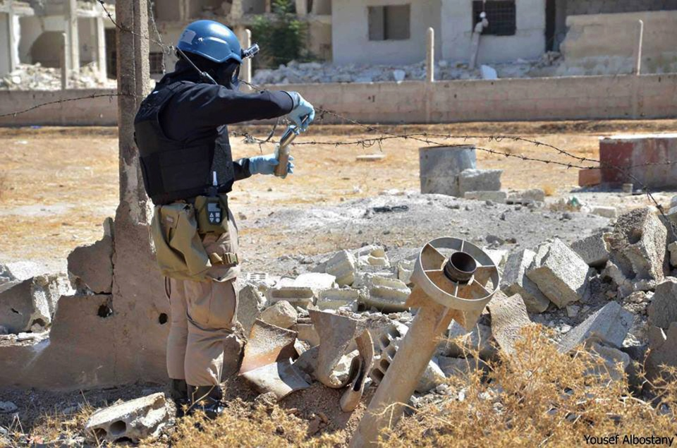A member of UN investigation team taking samples of sands near a part of a missile is likely to be one of the chemical rockets according to activists, in Damascus countryside of Ain Terma, Syria, Wednesday, Aug. 28, 2013. (United Media Office of Arbeen)