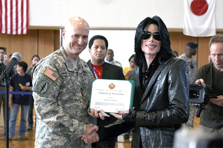 Col. Robert M. Waltemeyer, left, garrison commander of Camp Zama, presents U.S. pop icon Michael Jackson a certificate of appreciation to thank Jackson for visiting about 1,600 servicemembers, their families, and U.S. civilian and Japanese national employees at Camp Zama, south of Tokyo, on Saturday March 10, 2007. (AP / U.S. Army, Slade Walters)
