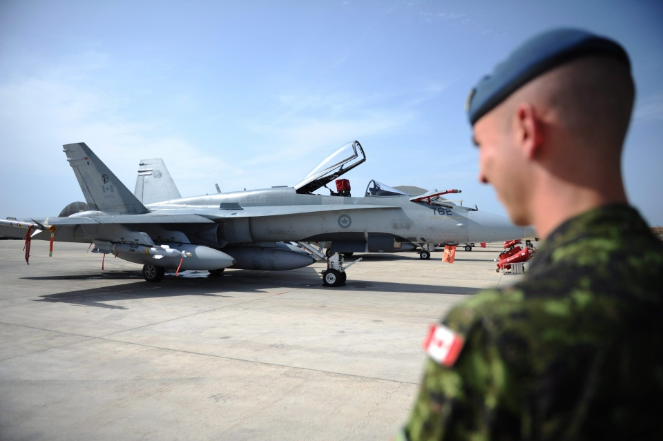 A Canadian soldier looks at a CF-18 Hornet as it sits loaded for flight at Camp Fortin on the Trapani-Birgi Air Force Base in Trapani, Italy, on Thursday, Sept. 1, 2011. (Sean Kilpatrick / THE CANADIAN PRESS)