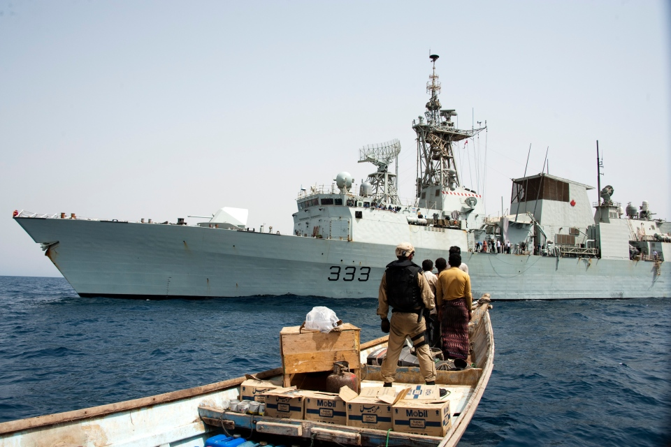 A member of HMCS Toronto's boarding party guards individuals onboard a skiff during a narcotics seizure in the Red Sea as part of Operation Artemis on June 28, 2013.  (Cpl. Malcolm Byers / HMCS Toronto)