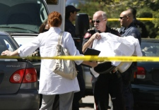 Calgary police Insp. Frank Reuser removes a one-year-old survivor from the scene after five bodies were discovered in a home in northwest Calgary on Wednesday, May 28, 2008. (Larry MacDougal / THE CANADIAN PRESS)