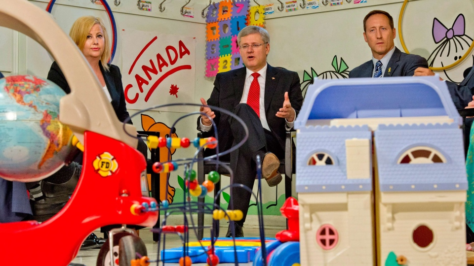 Lianna McDonald, Executive Director of the Canadian Centre for Child Protection and Justice Minister Peter MacKay, looks on as Prime Minister Stephen Harper speaks in Toronto on Thursday Aug. 29, 2013. (Frank Gunn / THE CANADIAN PRESS)