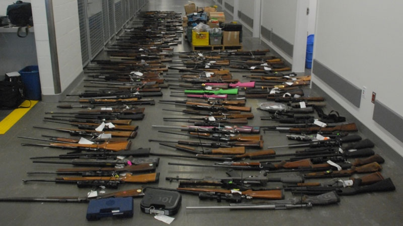 Police display the almost 200 guns allegedly seized from a home in Tatla Lake, B.C. earlier this month. Aug. 29, 2013. (Handout)
