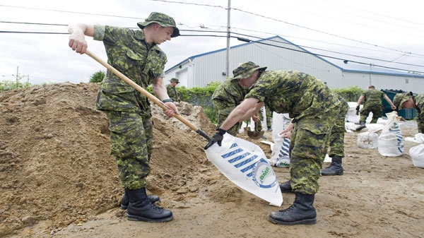Canadian Forces personnel fill sandbags in the town of Venice, Que., Tuesday, May 24, 2011. More troops headed to Quebec's Monteregie region overnight as water levels in the Richelieu River returned to a historic high. THE CANADIAN PRESS/Graham Hughes