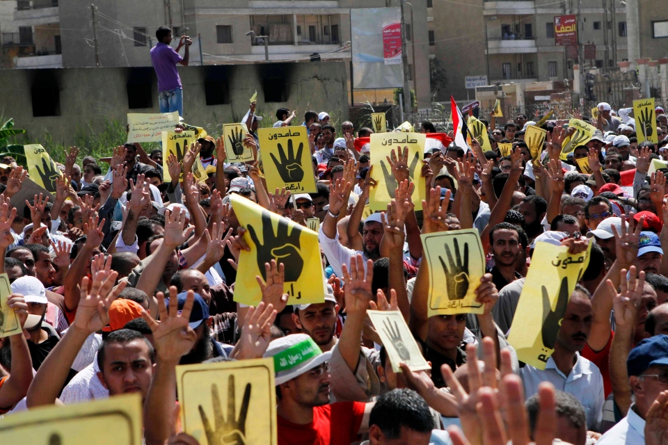 People raise their hands and banners to show a hand gesture of an open palm with four raised fingers during a protest in Beni Sueif, south of Cairo, Egypt, Friday, Aug. 30, 2013. (AP / Sabry Khaled, El-Shorouk)