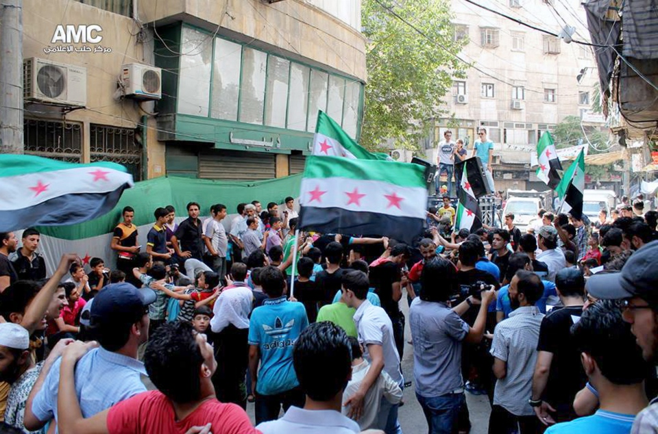 Anti-Syrian regime protesters hold Syrian revolution flags during a demonstration in the neighborhood of Bustan Al-Qasr in Aleppo, Syria, Friday, Aug. 30, 2013. (Aleppo Media Center AMC)