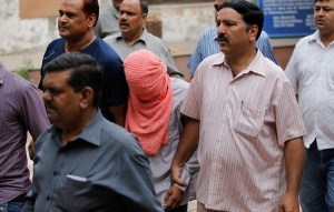 Delhi police officers escort a juvenile accused of rape, outside the Juvenile justice board in New Delhi, India, Saturday, Aug. 31, 2013. (AP / Altaf Qadri)