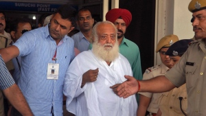 Controversial spiritual guru Asaram Bapu, center, is brought for interrogation by police at Jodhpur airport in Jodhpur, India, Sunday, Sept. 1, 2013. Bapu was arrested early Sunday on a rape charge filed by a teen-age girl in the northwestern Indian state of Rajasthan, police said. (AP / Sunil Verma)