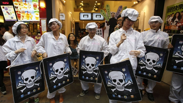 In this Saturday, May 7, 2011 file photo, local and mainland Chinese universities' students, dressed as the Foxconn workers, hold mock iPads with a skeleton print outside an Apple Premium Reseller shop in Hong Kong. (AP Photo/Kin Cheung, File)