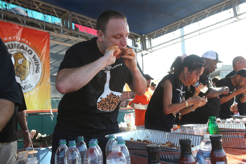 Competitive eater Joey Chestnut devours a chicken wing, on his way to eating a record 191 chicken wings in 12 minutes, at the National Buffalo Wing Festival, in Buffalo, N.Y., Sunday, Sept. 1, 2012. (The Buffalo News, Robert Kirkham)