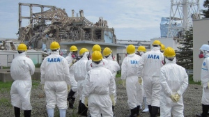 In this photo released by Tokyo Electric Power Co. (TEPCO), International Atomic Energy Agency (IAEA) experts and TEPCO staff stand near Unit 3 during the United Nations nuclear fact-finding mission's inspection tour to the tsunami-crippled Fukushima Dai-ichi nuclear complex in Okuma town, Fukushima Prefecture, northeastern Japan, Friday, May 27, 2011. (AP / Tokyo Electric Power Co.)