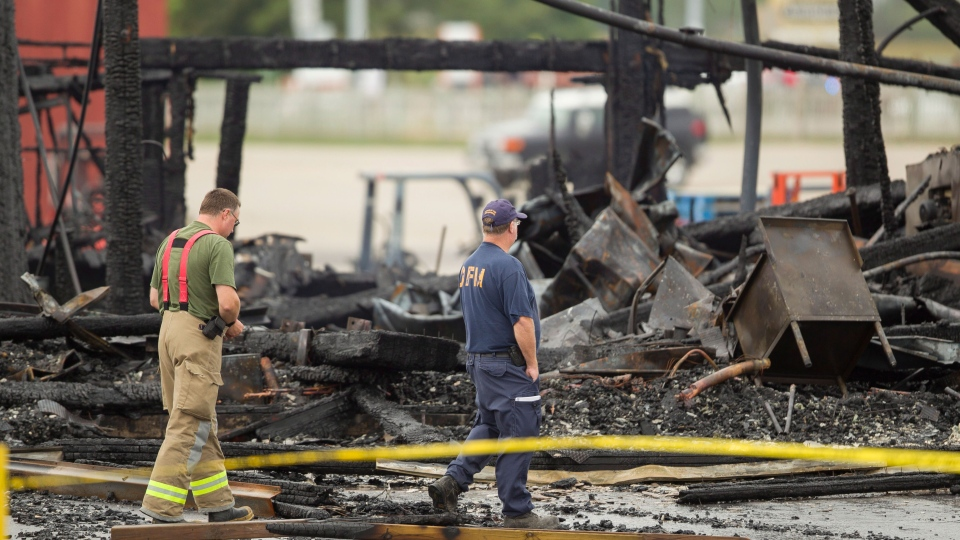Investigators from the Ontario Fire Marshal's office survey the remains of the main building at the St. Jacobs Farmers Market in Waterloo, Ontario, Monday, Sept. 2, 2013. (Geoff Robins / THE CANADIAN PRESS)