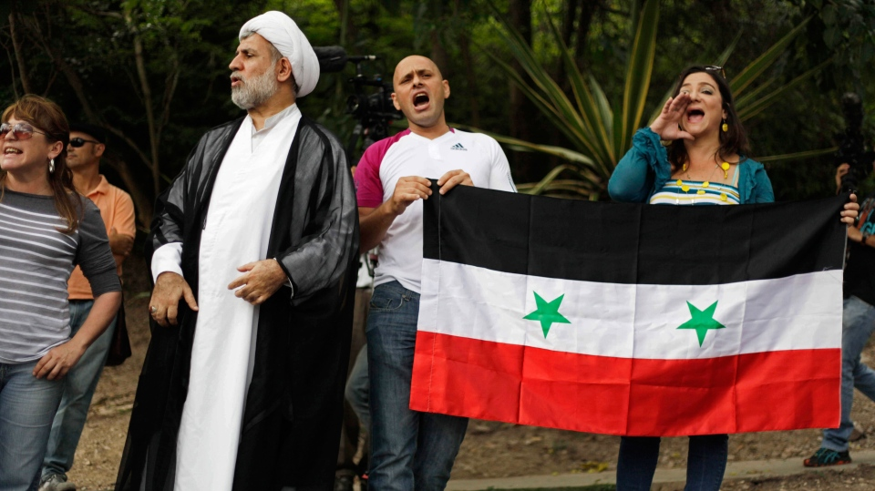 Venezuelans of Arab descent hold a Syrian flag as they gather in solidarity with the Syrian people and protest any military action in Syria by the U.S., outside the U.S. embassy in Caracas, Venezuela, Monday, Sept. 2, 2013. (AP / Ariana Cubillos)