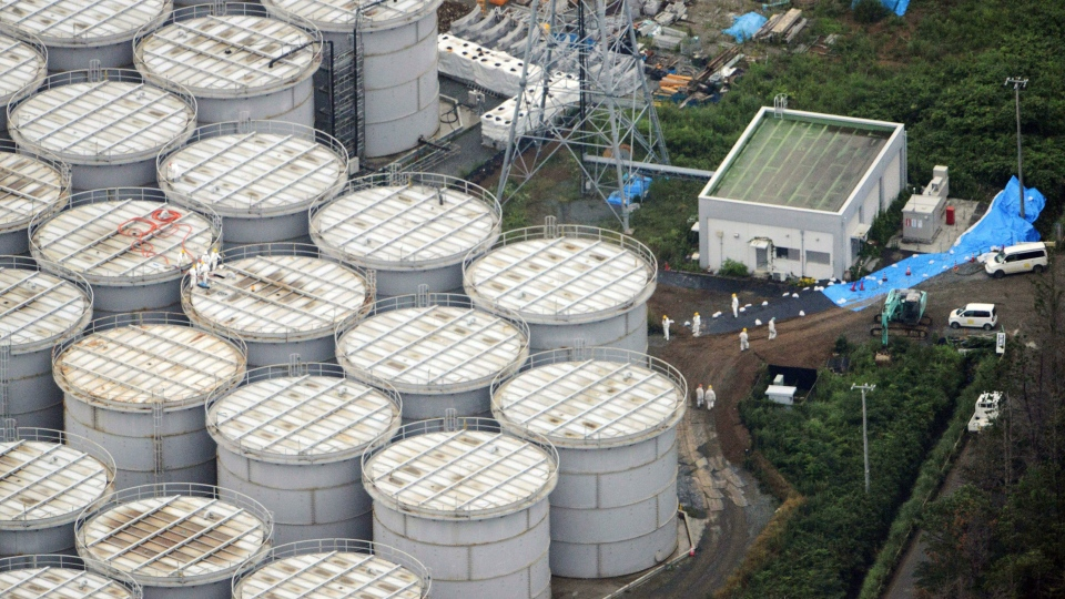 Workers stand on storage tanks at the Fukushima Dai-ichi nuclear plant at Okuma town in Fukushima prefecture, northeastern Japan, Tuesday, Aug. 20, 2013. (Kyodo News)