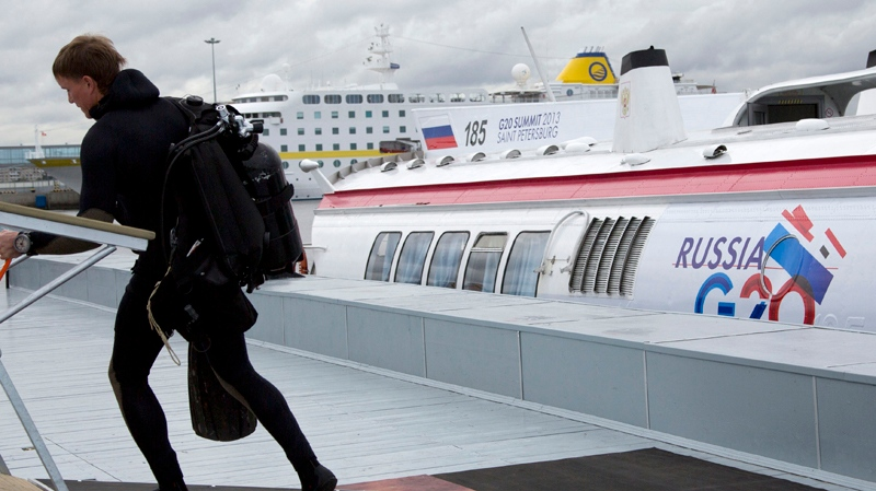 A military scuba diver walks by a shuttle boat for the upcoming G20 summit of world leaders in St. Petersburg, Russia on Tuesday Sept. 3, 2013. (AP / Virginia Mayo)