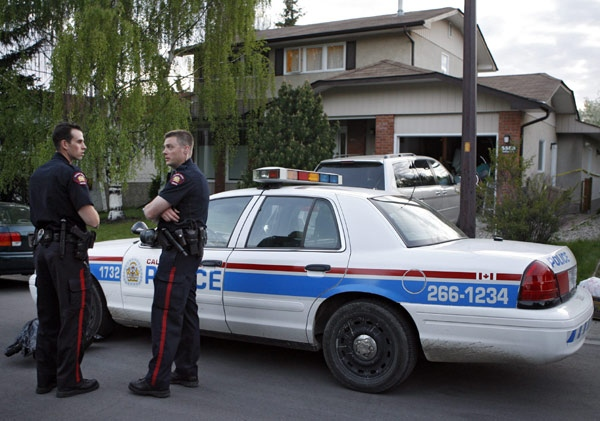 Police officers stand in front of a house that was the scene of a multiple murder in Calgary, Wednesday, May 28, 2008. (Jeff McIntosh / THE CANADIAN PRESS)