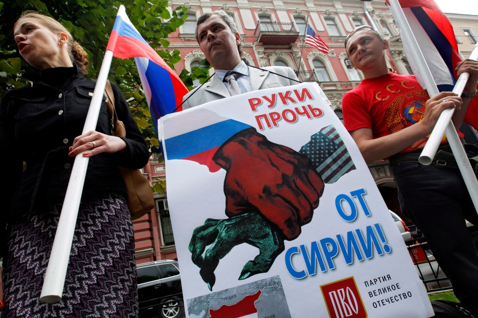Russian members of pro-Kremlin parties take part in a picket against a possible U.S. military action against Syria near the U.S. Consulate in St.Petersburg, Russia, Monday, Sept. 2, 2013. The banner reads 'Hands off Syria.' (AP / Dmitry Lovetsky)