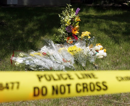 An impromtu memorial sits on the front yard of a house which was the scene of a multiple murder in Calgary, Thursday, May 29, 2008. (Jeff McIntosh / THE CANADIAN PRESS)