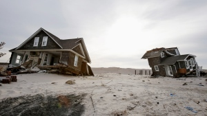 This Feb. 22,2013 file photo shows Two heavily damaged homes on the beach in Mantoloking, N.J., from Superstorm Sandy. Man-made global warming may decrease the likelihood of the already unusual steering currents that pushed Superstorm Sandy due west into New Jersey in a freak 1-in-700 year path, researchers report. (AP / Mel Evans, File)