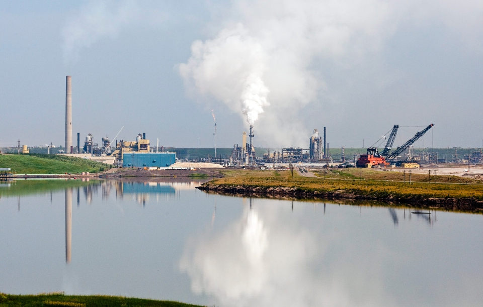 The Syncrude oil sands facility is reflected in a tailings pond near Fort McMurray, Alta., Tuesday, July 10, 2012. (Jeff McIntosh / THE CANADIAN PRESS)