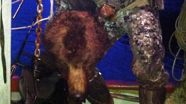 A hunter, later confirmed to be NHL player Clayton Stoner, is shown holding a grizzly bear head after a hunt in the Kwatna Etsuary in May 2013. (Robert S. Johnson / BearsForever.ca)