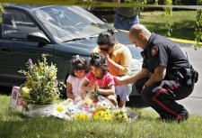 Simran Chandiramani, five, centre, and her twin sister Aarti, pray with their mother Alka and Calgary Police Serivce Const. Andrew Fuhrman after placing flowers on the front yard of a house which was the scene of a multiple murder in Calgary, Thursday, May 29, 2008. (Jeff McIntosh / THE CANADIAN PRESS)
