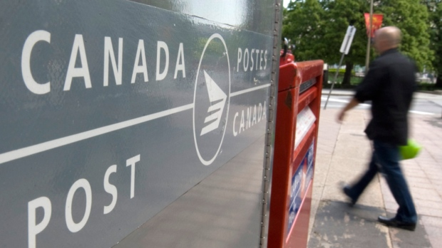 A man walks past Canada Post mail boxes in Ottawa, Monday, May 30, 2011. Canada Post's union announced they had given 72-hour strike notice. (Adrian Wyld / THE CANADIAN PRESS)