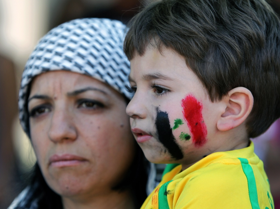 A Lebanese member the Syrian Social Nationalist Party carries her son with colors of the Syrian national flag is painted on his face, during a demonstration against a possible military strike in Syria, in front of the United Nations headquarters, in Beirut, Lebanon, Sunday, Sept. 8, 2013.  (AP / Bilal Hussein)