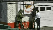 Police take down a Hells Angels sign from the front of a house in Trois Rivieres, Que., during a raid in this undated video image.