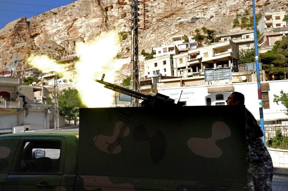 A Syrian military solider fires a heavy machine gun during clashes with rebels in Maaloula village, northeast of the capital Damascus, Syria on Saturday, Sept. 7, 2013.  (SANA)