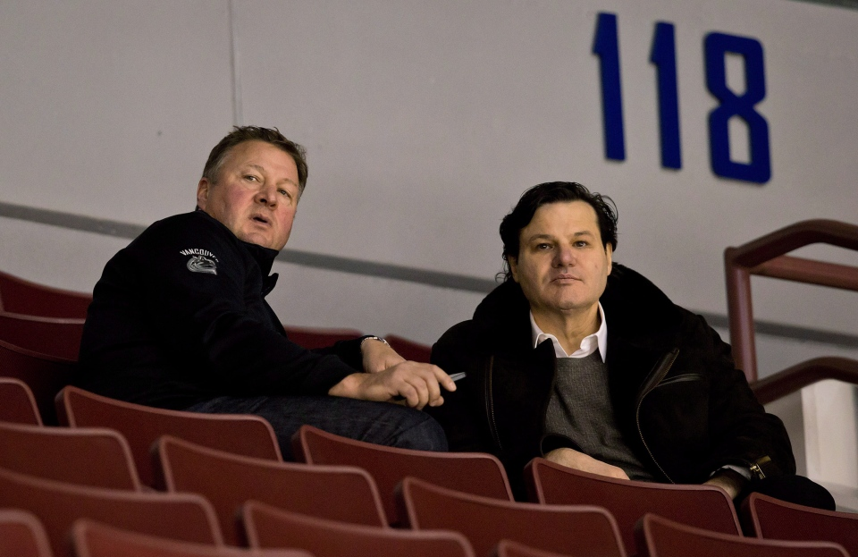 Vancouver Canucks' general manager Mike Gillis, left, and owner Francesco Aquilini watch players practice on the first day of the NHL hockey team's training camp in Vancouver, B.C., on Sunday January 13, 2013. THE CANADIAN PRESS/Darryl Dyck
