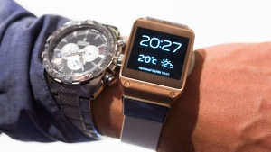 A man tries a Samsung Galaxy Gear, right, next to his regular watch after the presentation in Berlin, Germany, Wednesday, Sept. 4, 2013. Samsung has unveiled a highly anticipated digital wristwatch well ahead of a similar product expected from rival Apple. The so-called smartwatch is what some technology analysts believe could become this year's must-have holiday gift. Samsung unveiled the Galaxy Gear on Wednesday in Berlin ahead of the annual IFA consumer electronics show. (AP Photo/Gero Breloer)