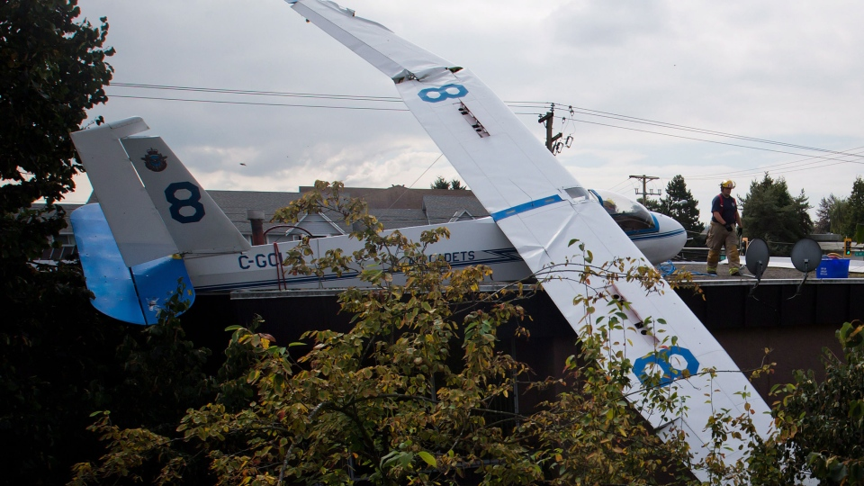 A firefighter walks past a glider that crashed on the roof of an apartment building and convenience store in Langley, B.C., on Sunday, Sept. 8, 2013. (Darryl Dyck / THE CANADIAN PRESS)