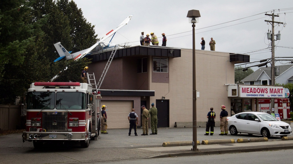 Firefighters and an RCMP officer stand on the roof of an apartment building and convenience store where a glider crashed in Langley, B.C., on Sunday September 8, 2013. (Darryl Dyck / THE CANADIAN PRESS)