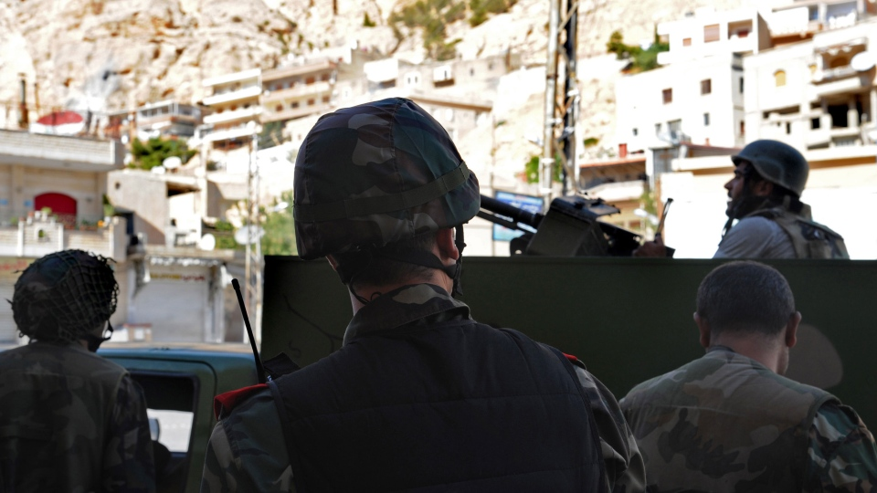 Syrian government forces stand guard in Maaloula village, northeast of the capital Damascus, Syria, Saturday, Sept. 7, 2013. (SANA)